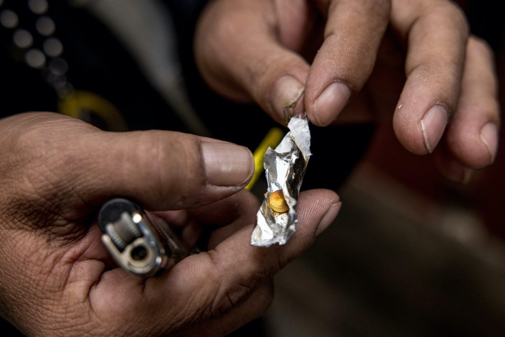 A motorbike taxi driver holds a yaba methamphetamine pill while demonstrating how he consumes the drug during an interview with AFP in Bangkok. (AFP)