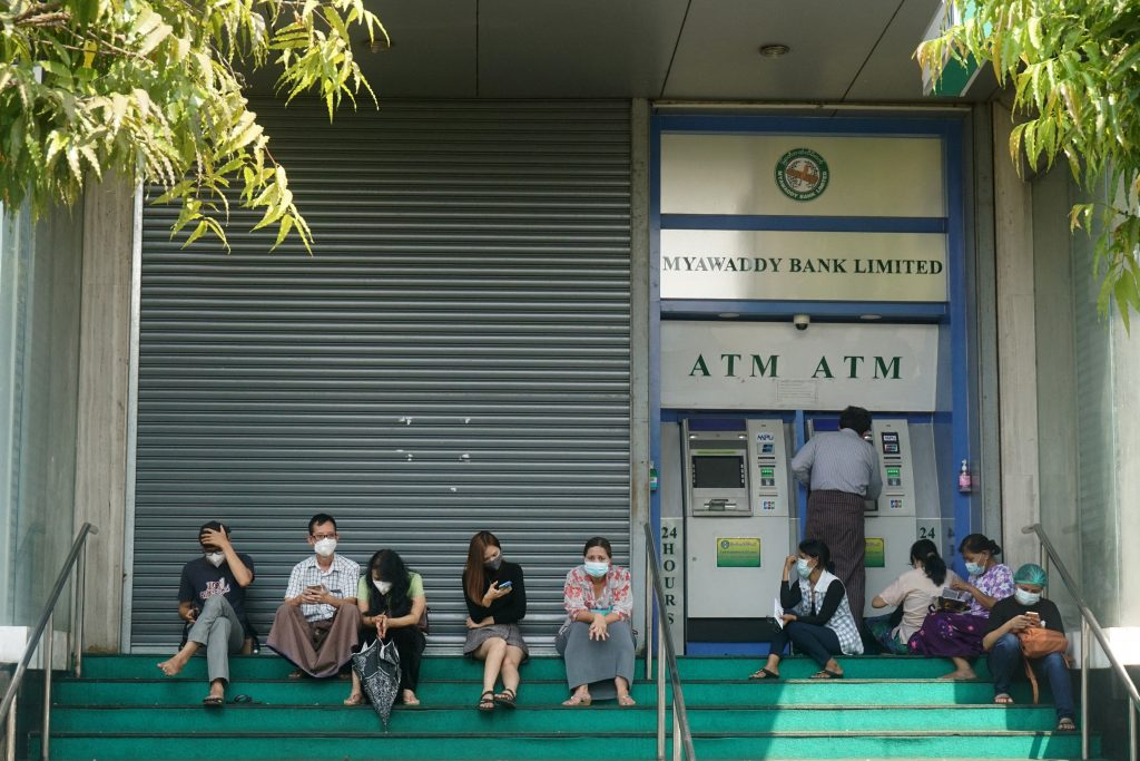 People wait to withdraw money from an ATM outside a branch of Myawaddy Bank in Yangon on February 23. (AFP)