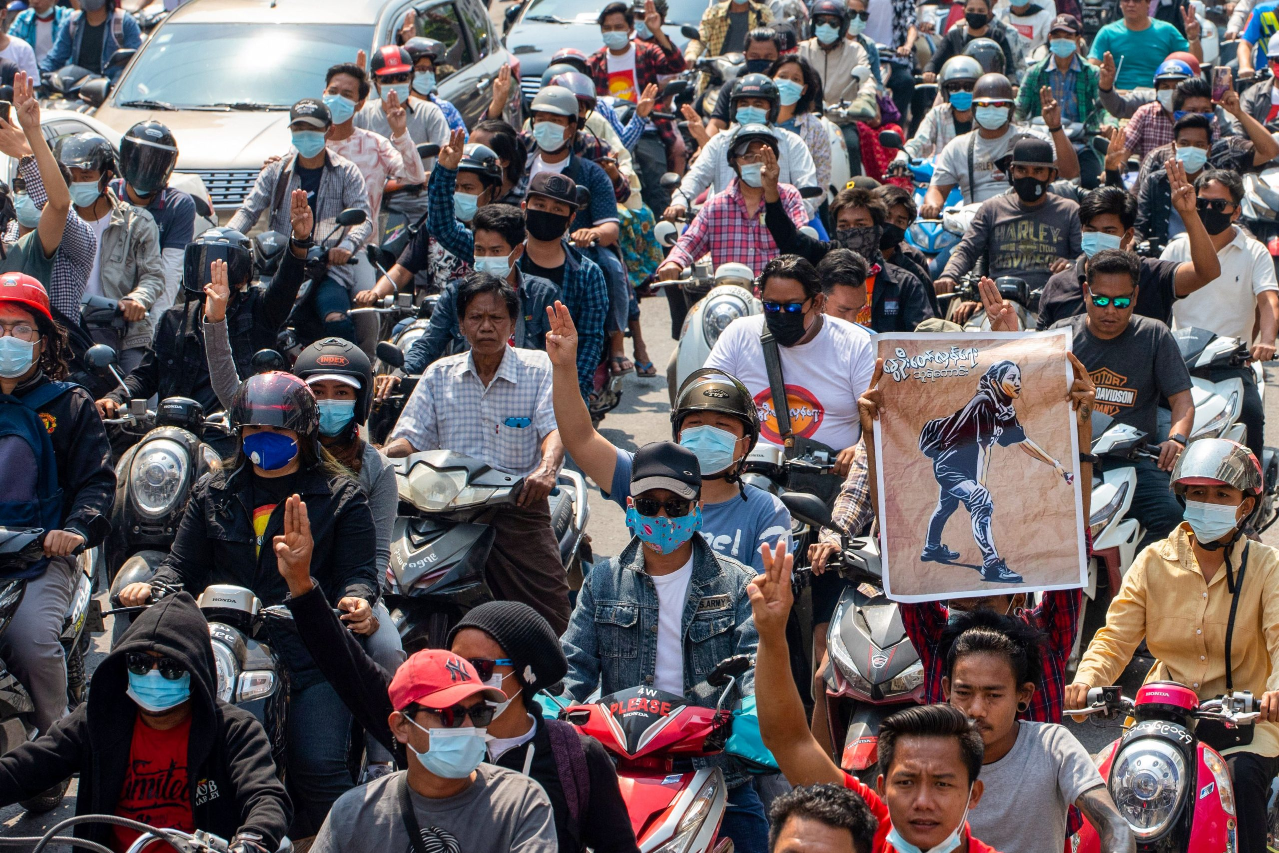 A man holds up a poster featuring protester Ma Kyal Sin during her funeral procession in Mandalay today. (AFP)