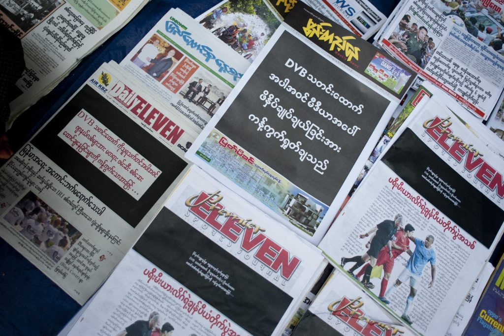"""Newspapers including the Democratic Voice of Burma display black front pages at a Yangon news stall on April 11, 2014, after a DVB reporter was convicted of """"disturbing a civil servant"""" for trying to get an interview with an education official. (AFP)"""