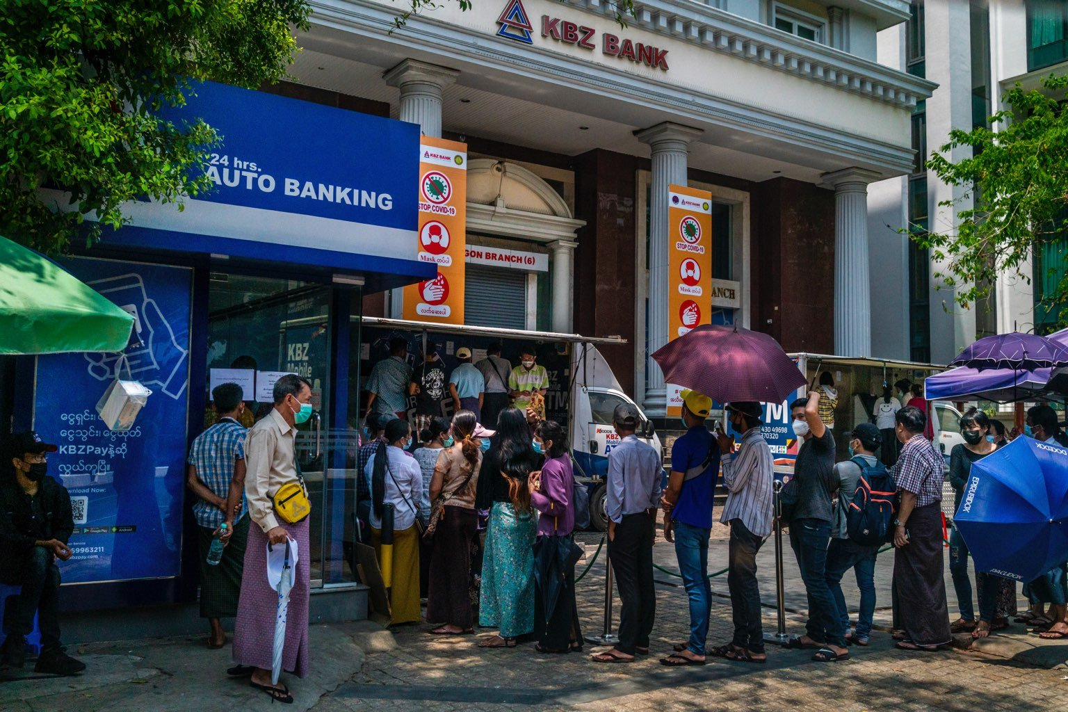 Customers queue at a KBZ Bank ATM on March 22. Myanmar's largest private bank has reopened just five of its 144 Yangon branches, according to its website, leaving customers reliant on mobile banking and ATMs. (Frontier)