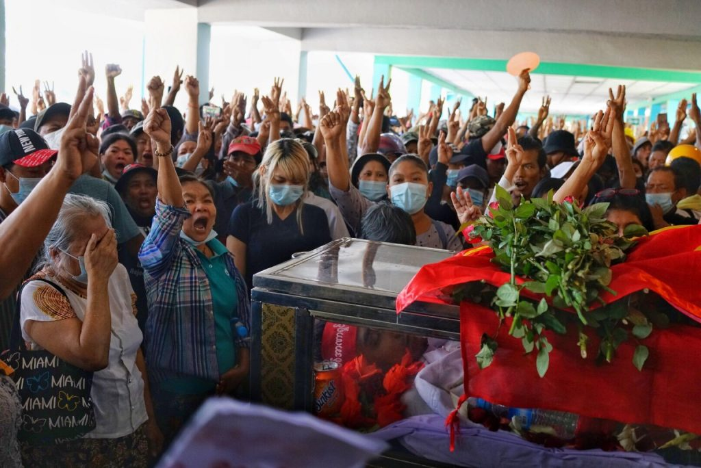 Mourners chant and give a three-finger salute at the funerals for three men killed in Yangon's North Okkalapa Township on March 3. (Frontier)