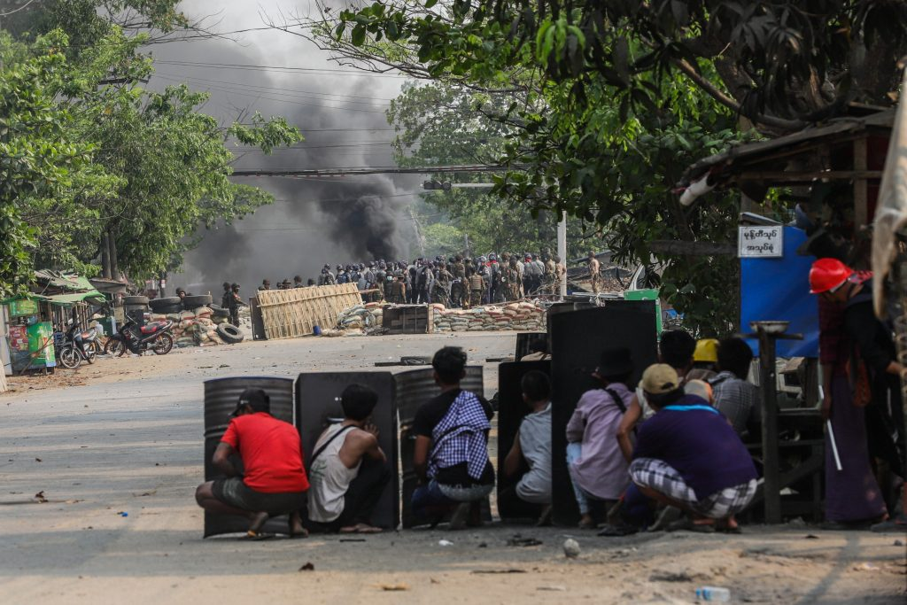 Protesters with makeshift shields face off against police and soldiers in Hlaing Tharyar on March 14, a day that saw at least 58 civilians killed, according to local volunteer medical groups. (Frontier)