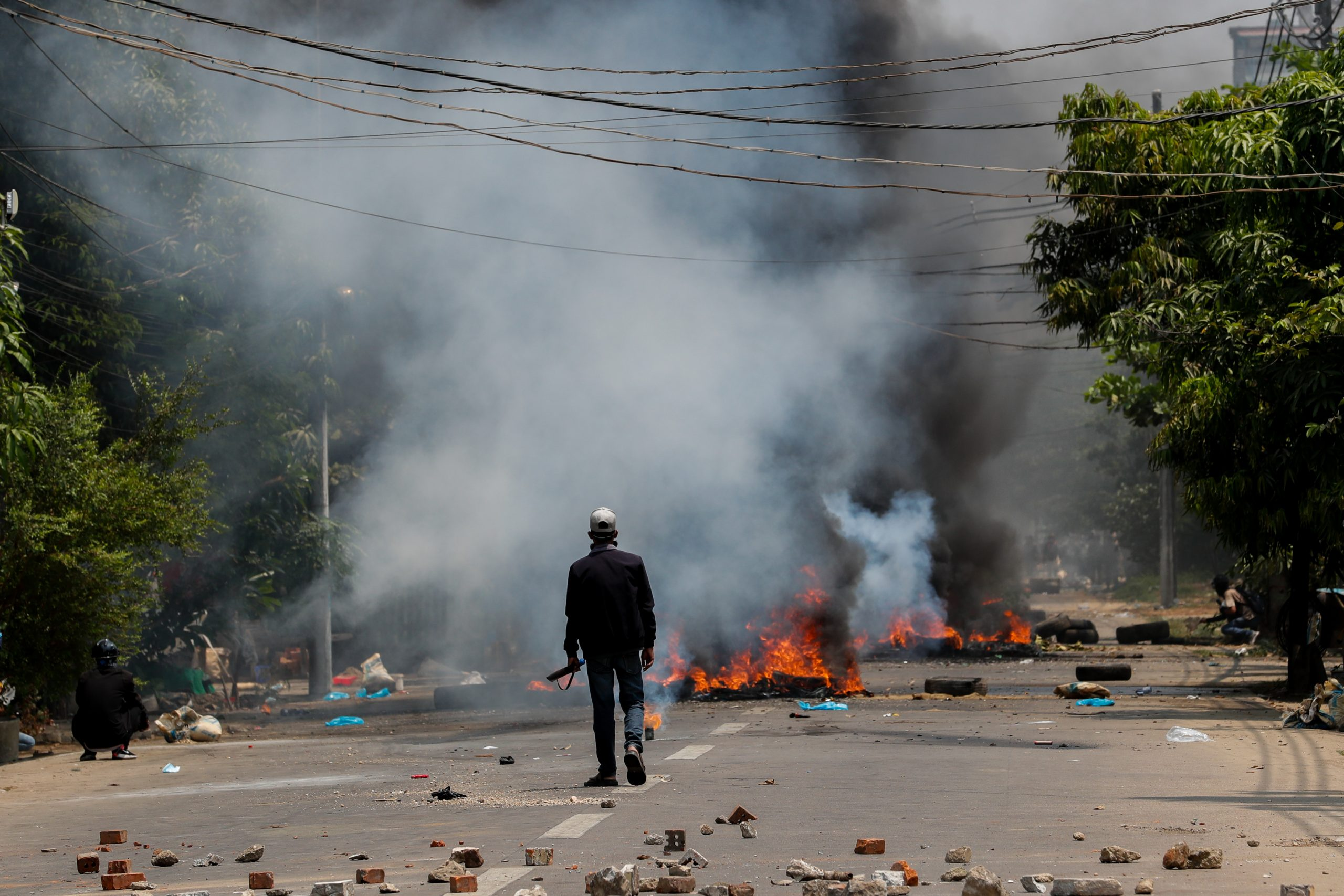 A protester in Yangon's Thaketa Township walks along a smoke-filled road earlier today. (Frontier)