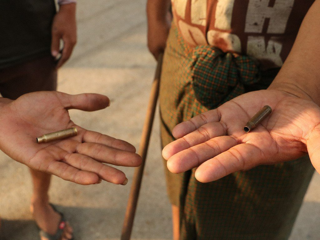 Residents of Yangon's South Dagon Township display bullet casings from live rounds fired at civilians by soldiers and police there on March 28, a brutal day of crackdowns that left multiple dead and included the military's use of live grenades on civilians. (Frontier)