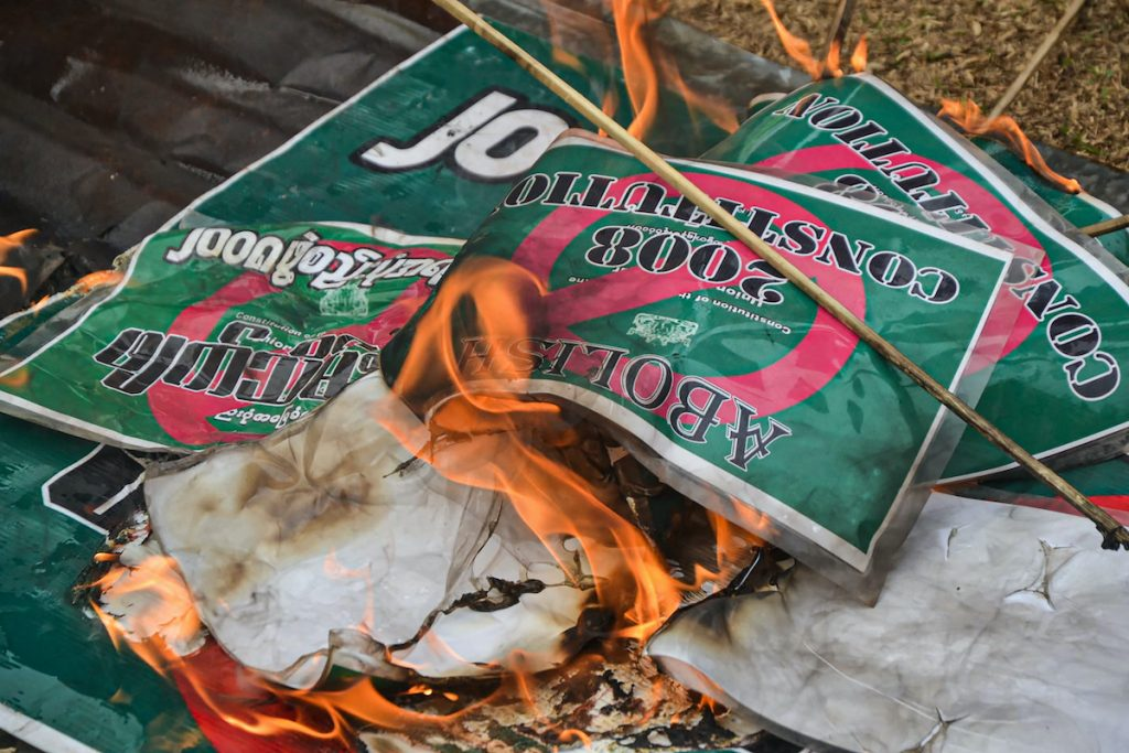 Signs about the 2008 Constitution are burnt during a demonstration by supporters Karen National Union supporters against the military coup in Kawkareik Township, eastern Karen State on April 2. (AFP)