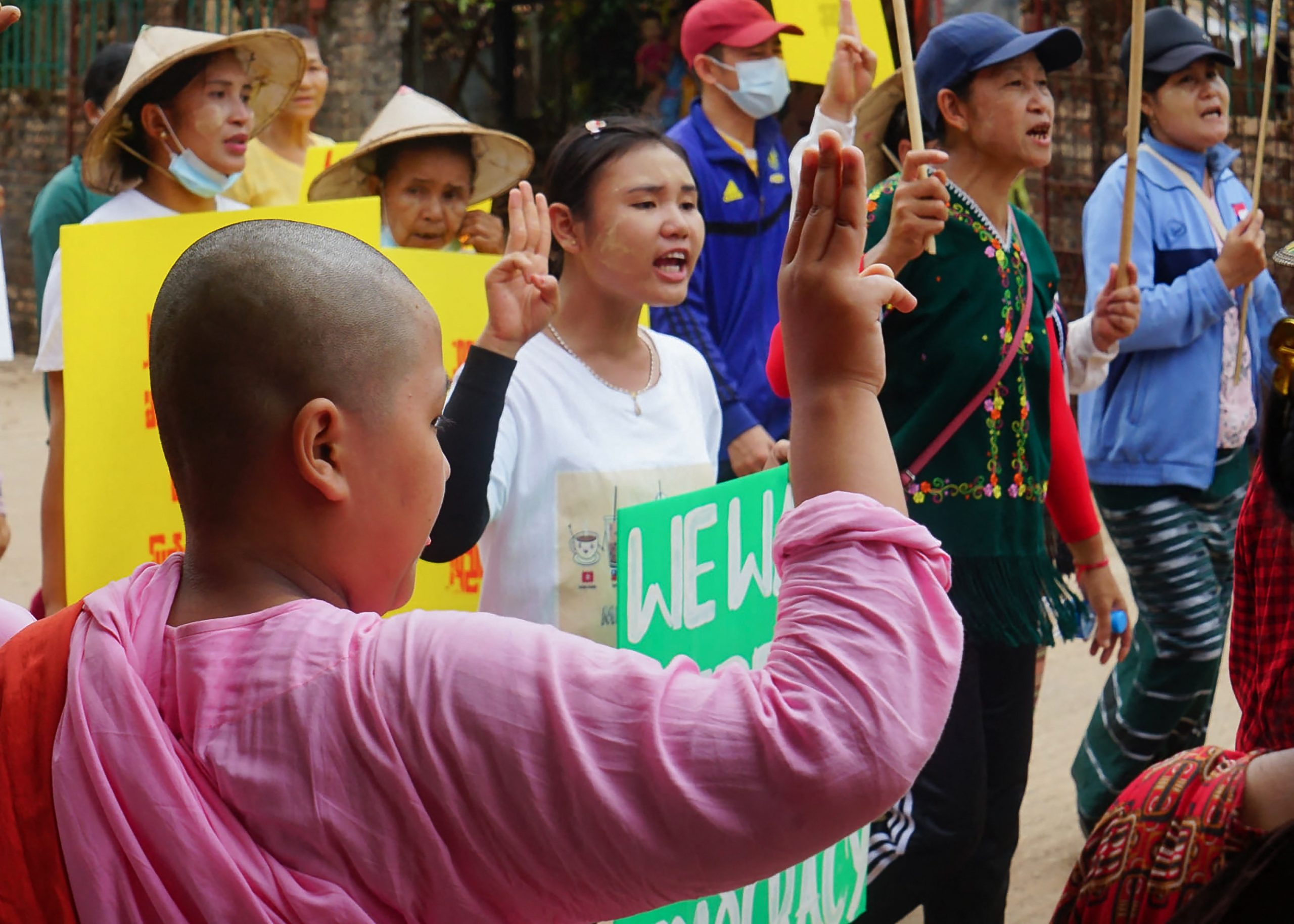 A young Buddhist novice nun holds up the three-finger salute to anti-coup protesters in Karen National Union-administered Dooplaya District, Kayin State, on April 2. (KNU / AFP)