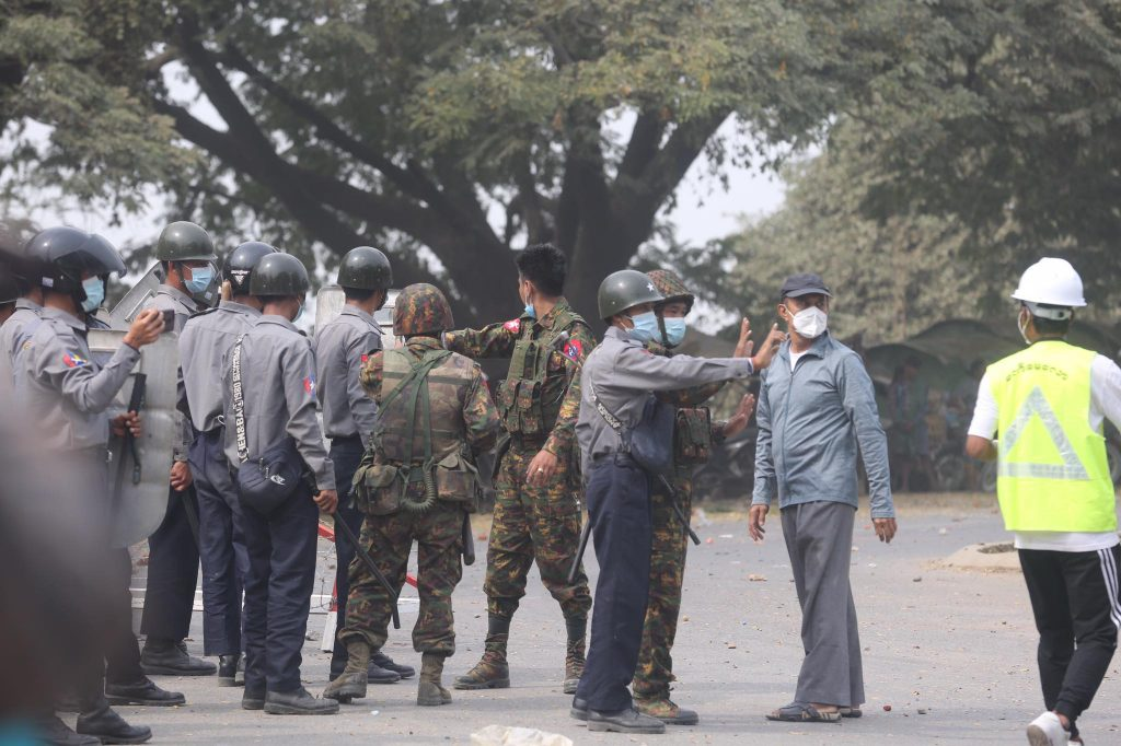 Men wear helmets normally worn by soldiers over baggy, ill-fitting police shirts and trousers while accompanying soldiers at a protest in Mandalay on February 20, when security forces shot dead two protesters near a dockyard in the city. (Frontier)