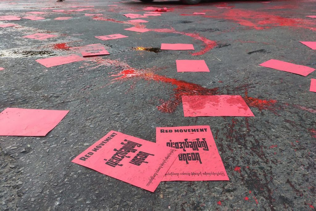 "Anti-coup protesters in Yangon splash red paint on the ground and scatter flyers on April 10 in a student-led ""Red Movement"" to commemorate the killing of hundreds of protesters by security forces. (Facebook / AFP)"