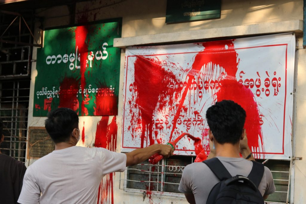 People splash red paint onto a ward administration office in Yangon's Tarme Township on April 11 to commemorate protesters slain by the military regime since the coup. (Facebook / AFP)