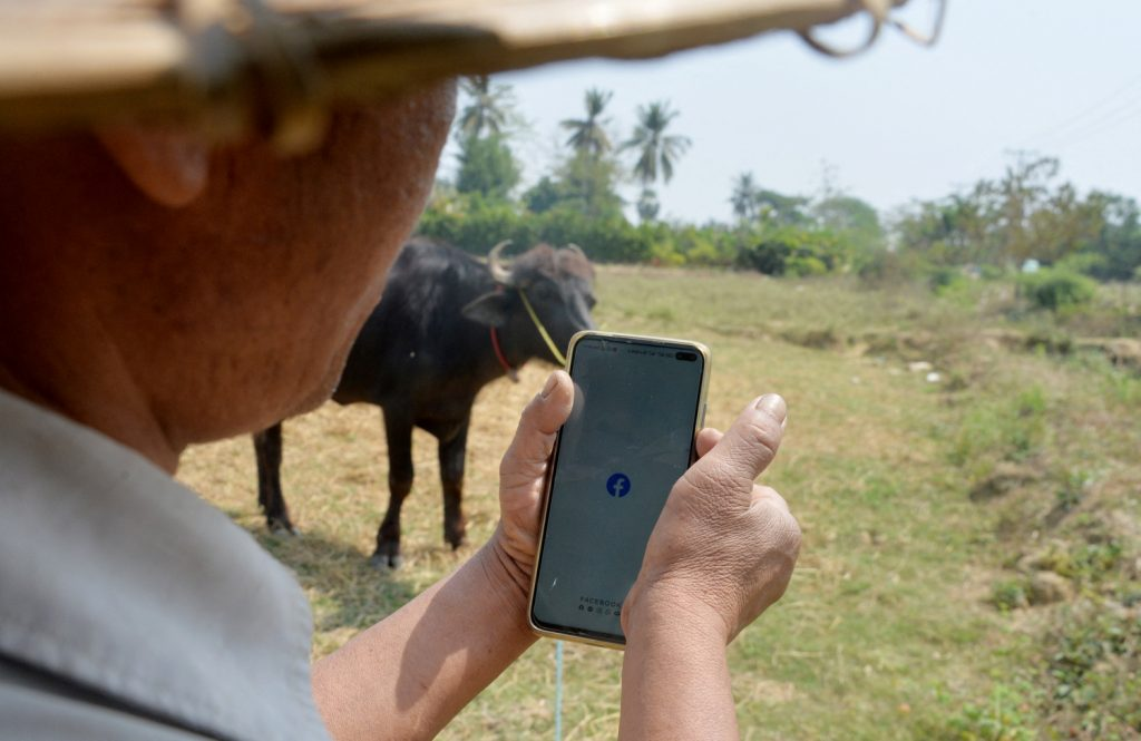 A farmer checks Facebook on his smartphone on March 16, shortly before the military regime cut mobile internet across Myanmar. (AFP)