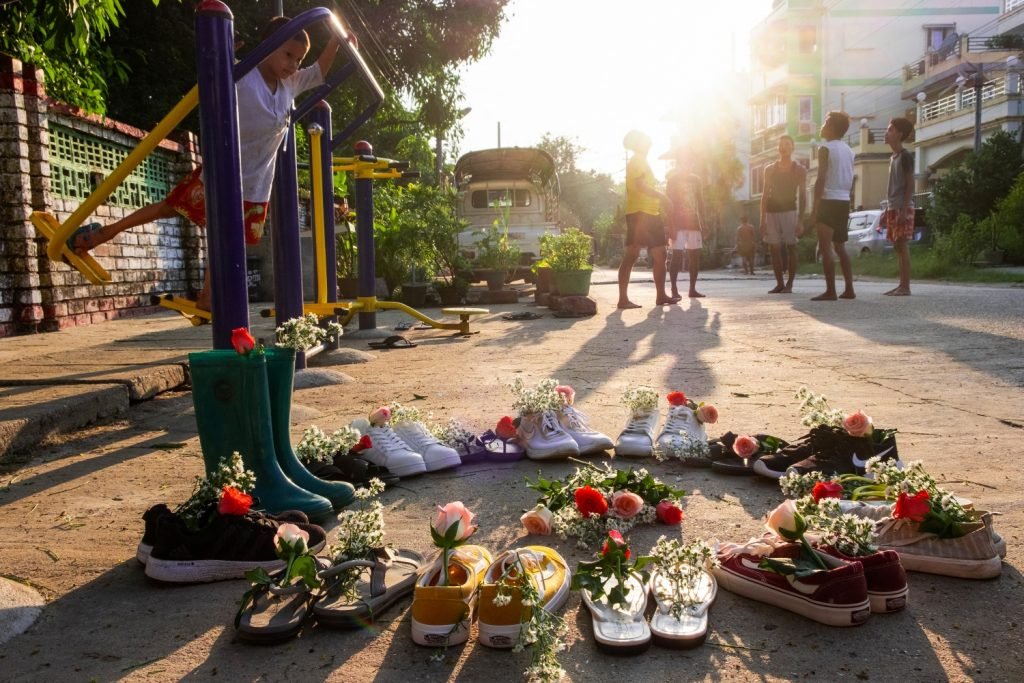 "A child plays near shoes displayed with flowers in Yangon's Insein Township, as part of the ""Marching Shoes Strike"" called on social media to protest against military rule. (AFP)"