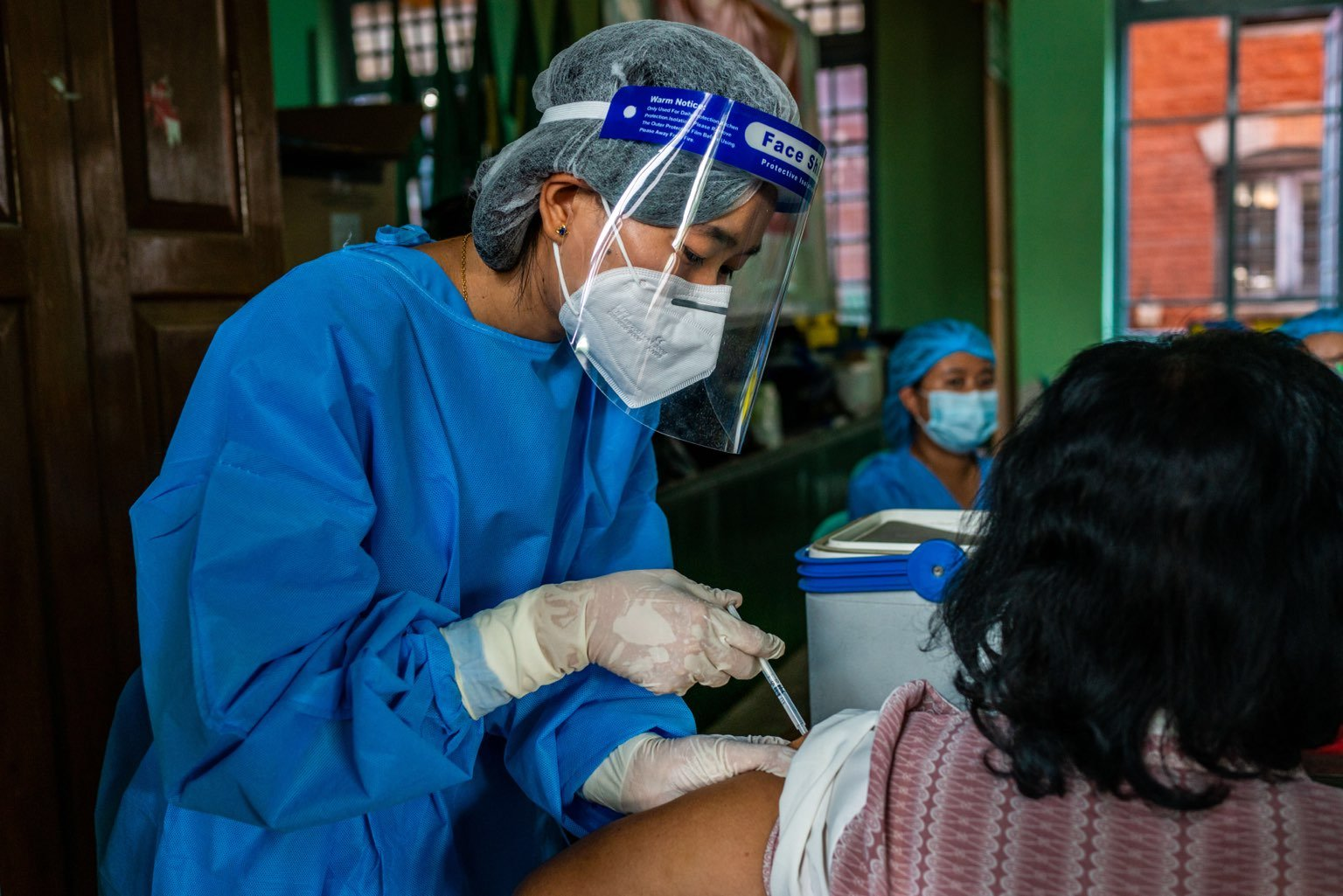 A health worker administers a first dose of the Indian-made Covishield COVID-19 vaccine at the Basic Education High School No. 4 in Botahtaung Township, Yangon, on February 5. (Frontier)