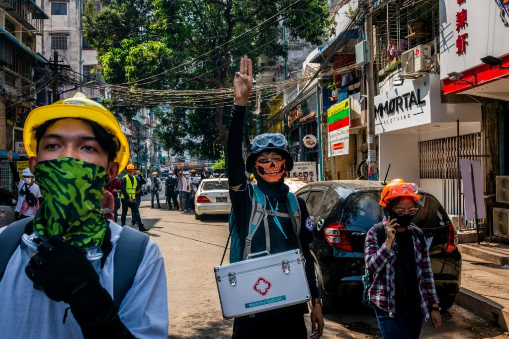 A rescue volunteer (centre) with a medical box raises the three-finger salute while serving at a protest in Yangon on March 3. (Frontier)