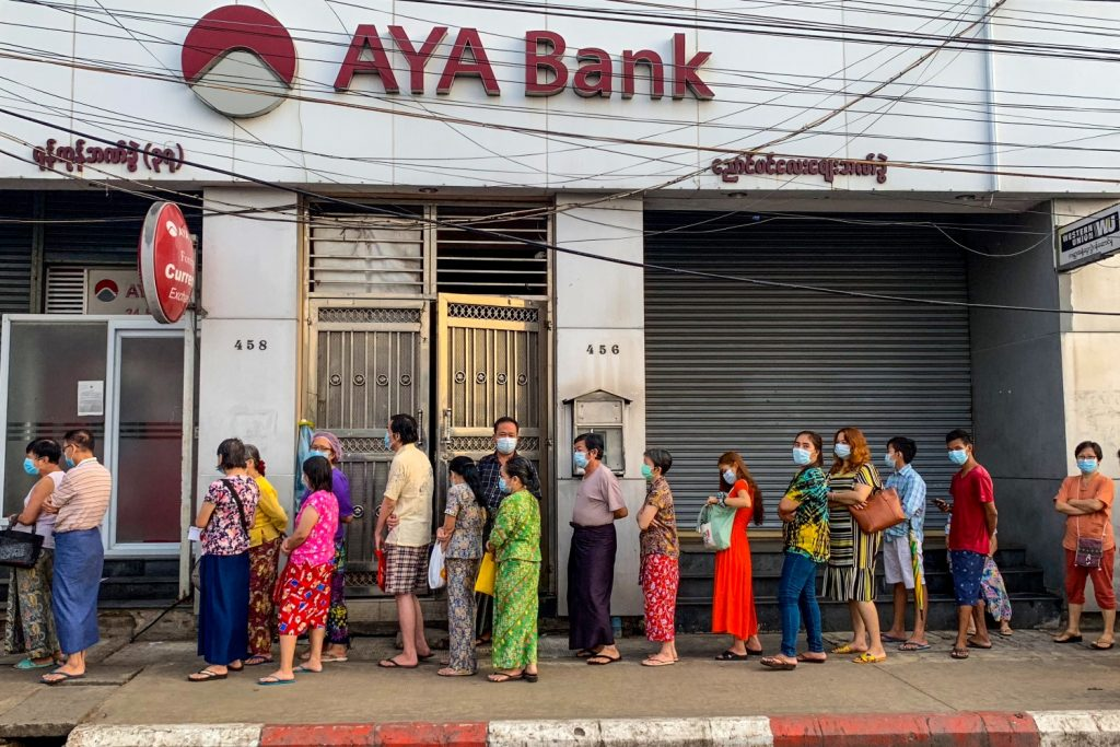 Yangon residents queue for cash outside a branch of AYA Bank on April 12. (AFP)