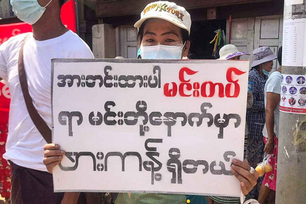 """The Tatmadaw's assault on the Chin State town of Mindat has inspired gestures of solidarity with the besieged militiamen and town residents from across Myanmar. Here, a protester in the Kachin State jade mining town of Hpakant on May 16 holds a placard reading, """"Stay strong Mindat, Hpakant is behind you."""" (Kachinwaves / AFP)"""
