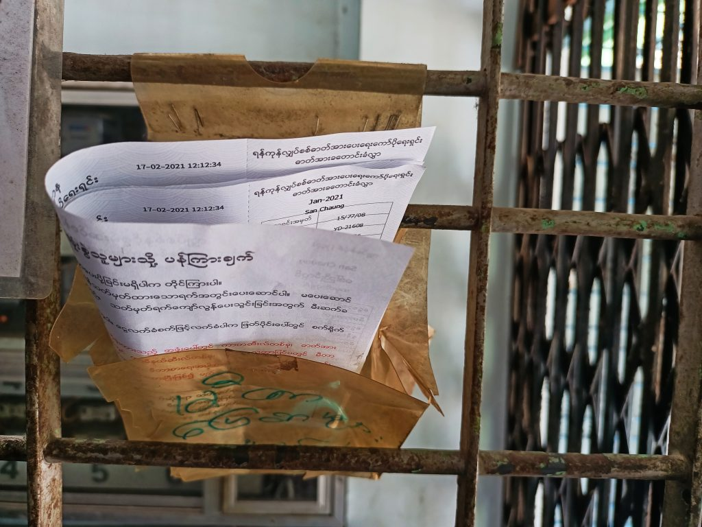An electricity bill sits outside an apartment in Sanchaung Township. (Frontier)