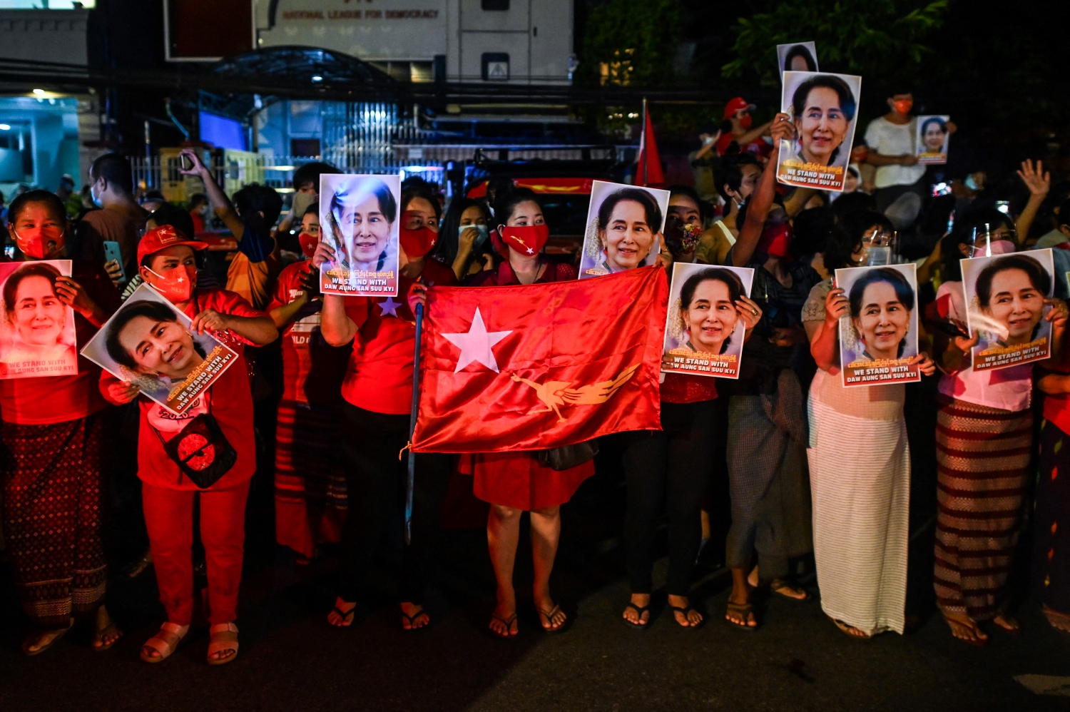 Supporters of the National League for Democracy hold portraits of party leader Daw Aung San Suu Kyi as they celebrate the NLD's 2020 election victory outside its headquarters in Yangon on November 9 last year, a day after the vote. (AFP)