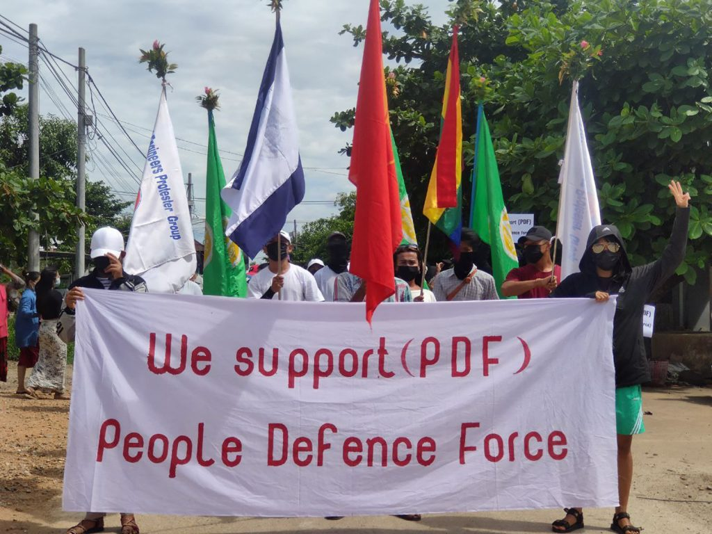 """Anti-coup protesters in the Tanintharyi Region capital Dawei on May 7 hold up a banner in support of the newly announced """"People's Defence Force"""". (Dawei Watch / AFP)"""