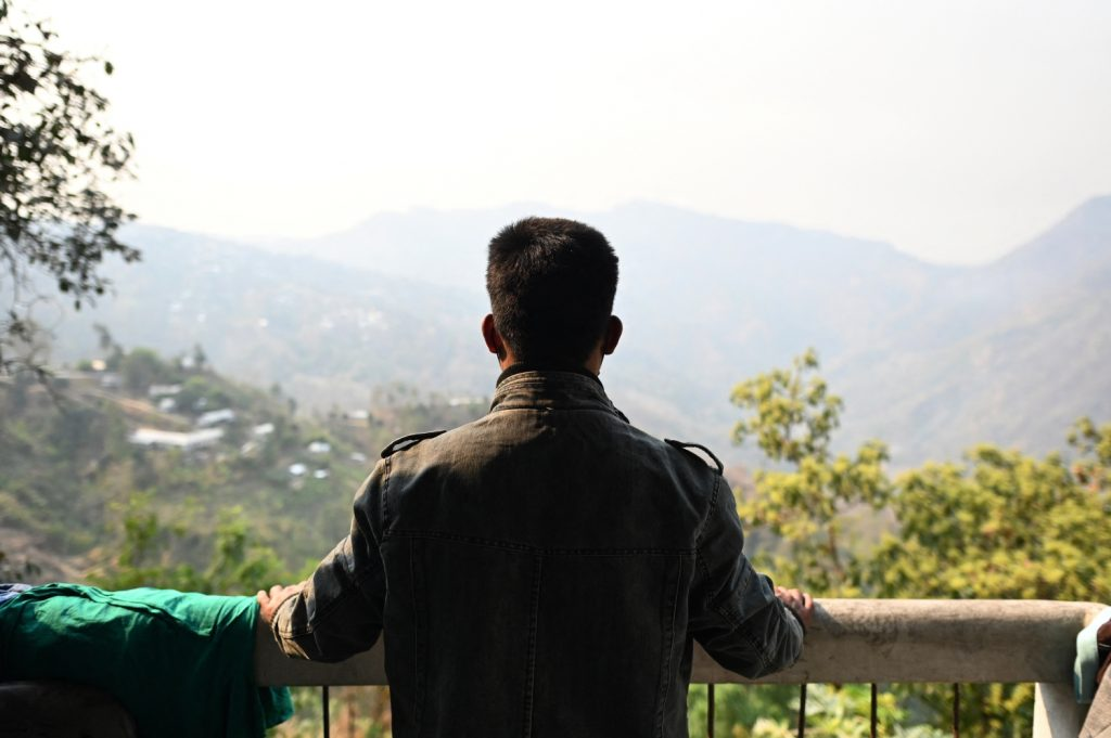 A Tatmadaw soldier who fled overland to India looks out from the balcony of a temporary shelter at an undisclosed location in Mizoram state on March 13. (AFP)