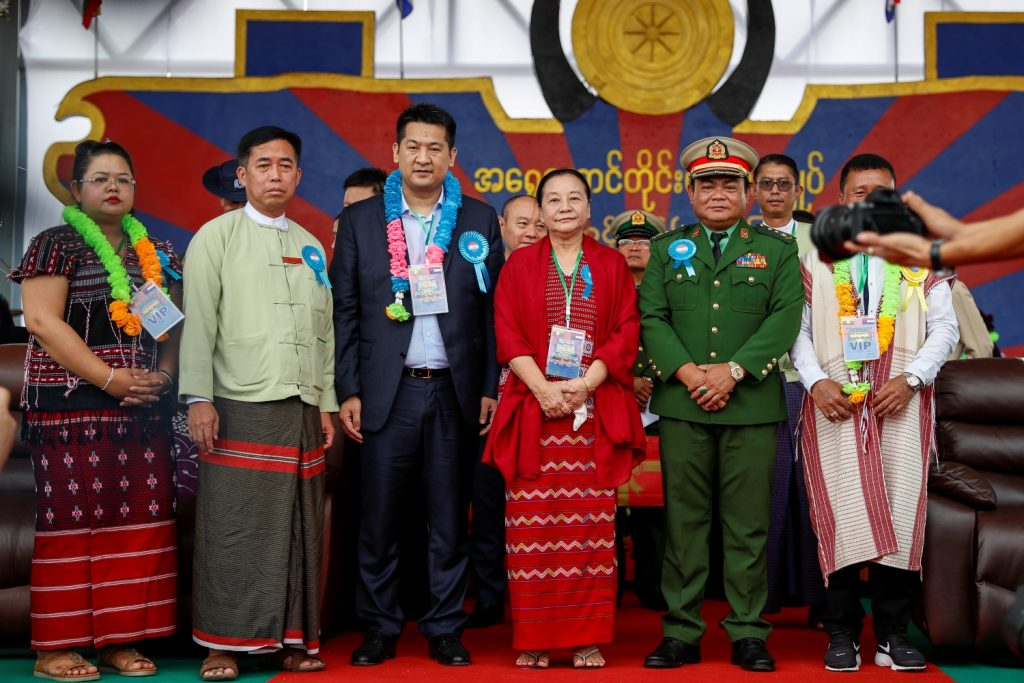 Dignitaries at the Karen BGF's ninth anniversary ceremony on August 20, 2019 included BGF chief Colonel Saw Chit Thu (right, in green uniform), Kayin State Chief Minister Nang Khin Htwe Myint (centre, in red) and the main investor in the controversial Yatai New City project in Shwe Kokko, ethnic Chinese businessman She Zhijiang, aka She Lunkai (centre-left, in Western suit). (Frontier)