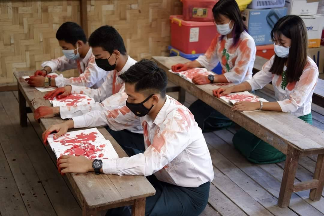 Students, protesting military rule, pose in a classroom setting while smeared with red paint to symbolise the blood of protesters slain by the junta. (Supplied)