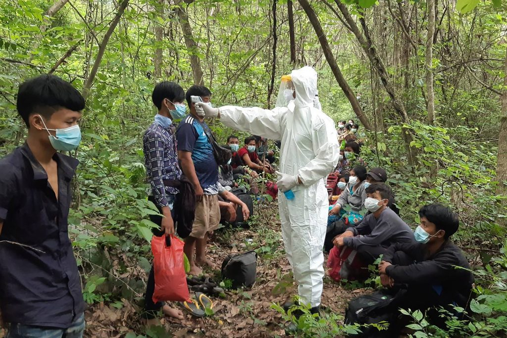 Thai military personnel in personal protective equipment (PPE) check the temperatures of migrants from Myanmar detained near the border in Prachuap Khiri Khan province on May 9.(APF/Royal Thai Army)