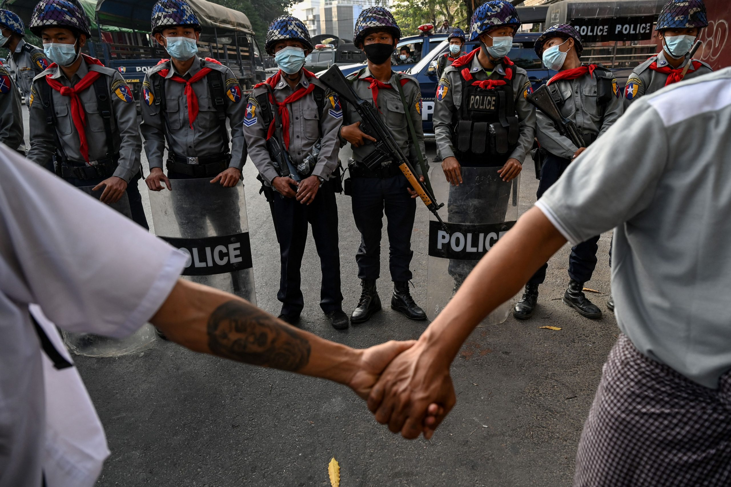 In this file photo taken on February 15, 2021 protesters hold hands to form a line in front of the police during a demonstration at the headquarters of the National League for Democracy (NLD) in Yangon. - With bars shuttered, universities empty and hook-up apps poleaxed by internet blackouts, dating got much harder in post-coup Myanmar, but young people are still finding love -- often in the heady rush of anti-junta protests. (Photo by STR / AFP)