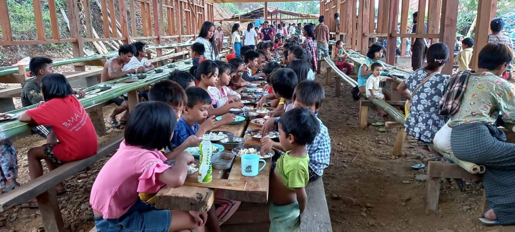 Children at an open-air dining site in the camp for displaced people at Lukse on May 22. (Supplied)