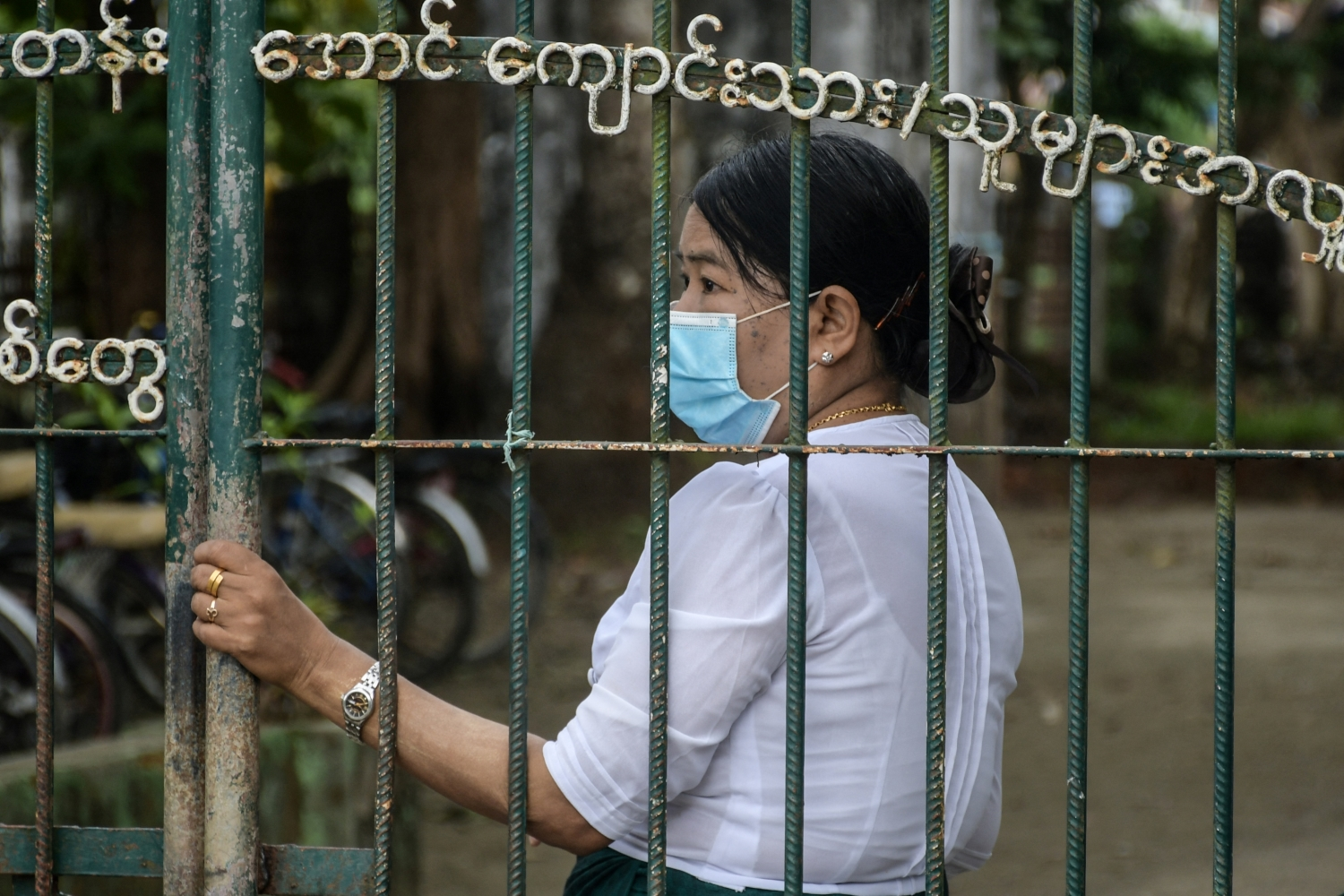 A teacher at a school gate on June 1, when the junta reopened schools across Myanmar with reportedly low attendance from children in most areas. (AFP)