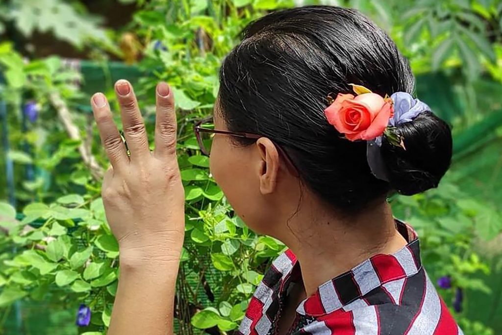 A woman in Yangon gives the three-finger salute while wearing flowers in her hair, as part of a social media campaign to mark the birthday of detained civilian leader Daw Aung San Suu Kyi on June 19. (Facebook, anonymous / AFP)