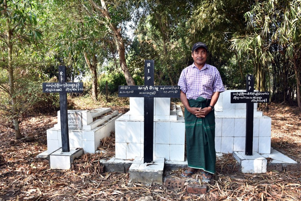 Kyoe Kone village resident Saw Kanarni stands at a cemetery with the graves of local people killed in the massacres of 1949. (Frontier)