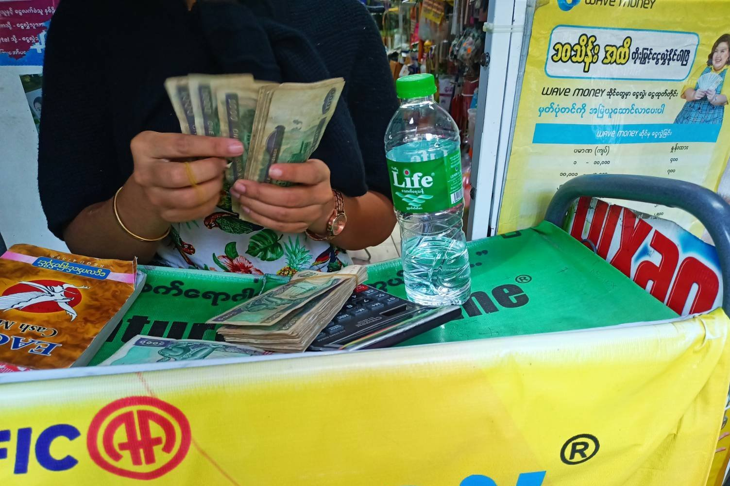 A Wave Money agent in Yangon counts cash before handing it over to a customer in May. Agents are charging 10 percent or more for cash withdrawals, in violation of company policy. (Frontier)