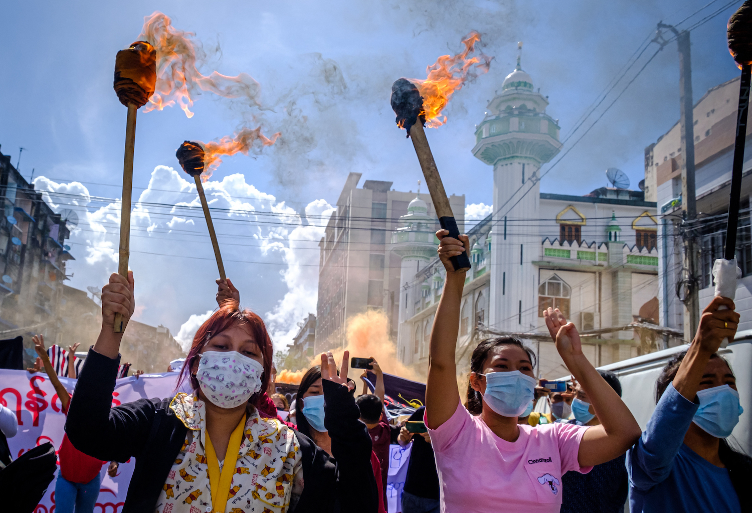 Women carry burning torches as they march during a demonstration against the military coup in Yangon on July 14. (AFP)