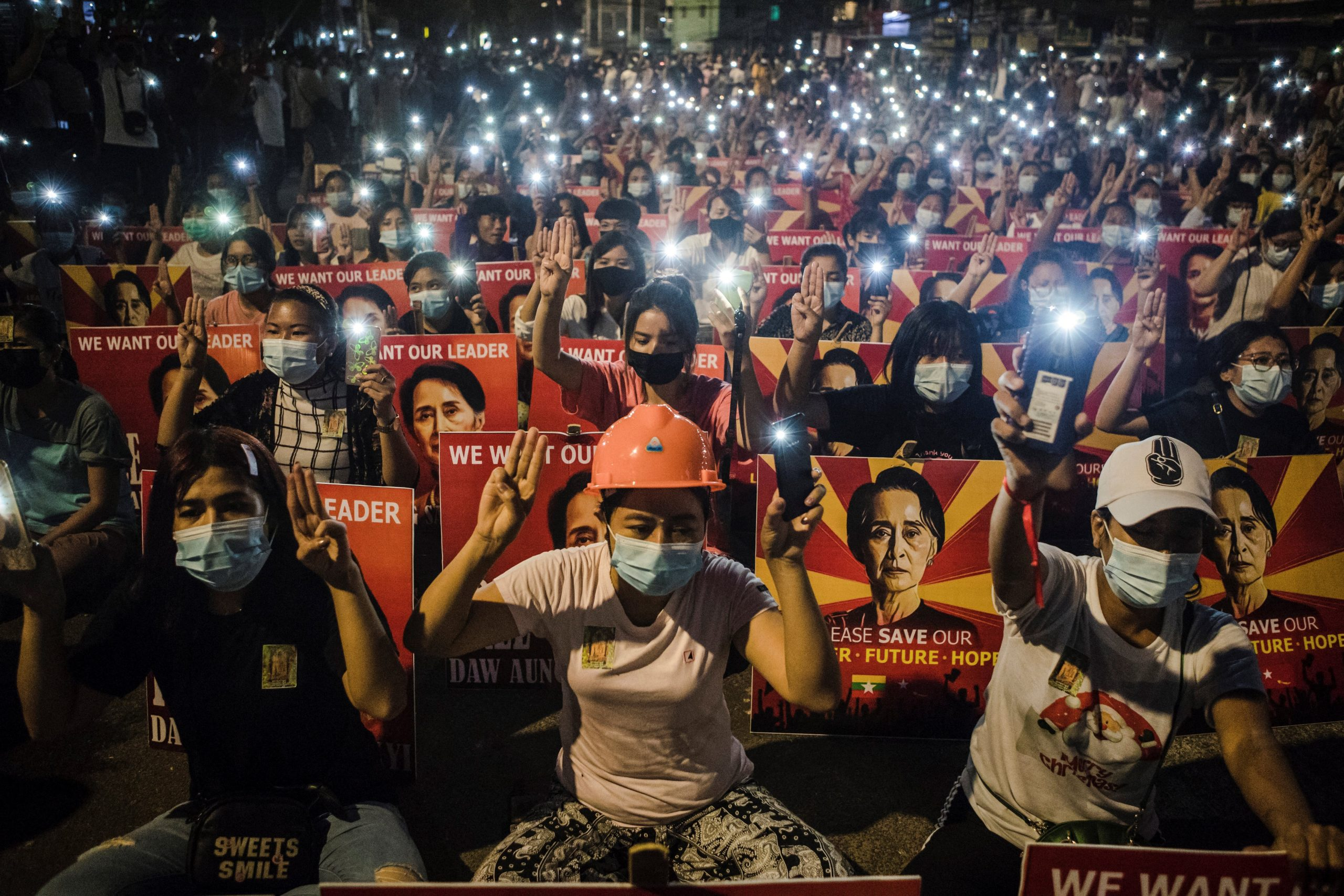 Taken on March 12, 2021, protesters hold up the three finger salute and placards with the image of Aung San Suu Kyi while using their mobile torches during a demonstration against the military coup in Yangon. (AFP)