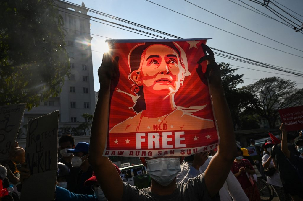 A protester holds up a poster of Daw Aung San Suu Kyi during an anti-coup demonstration outside the Central Bank building in Yangon on February 15. (AFP)