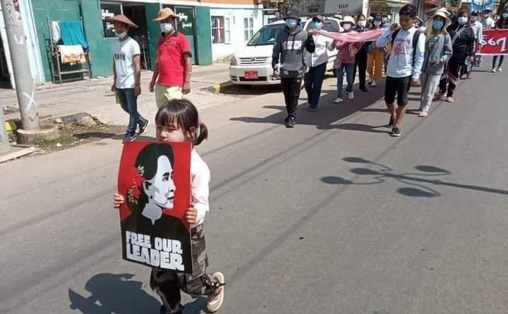 Su Htet Wine, 5, leads a protest march while holding a poster of Daw Aung San Suu Kyi in Mogok. (Supplied)