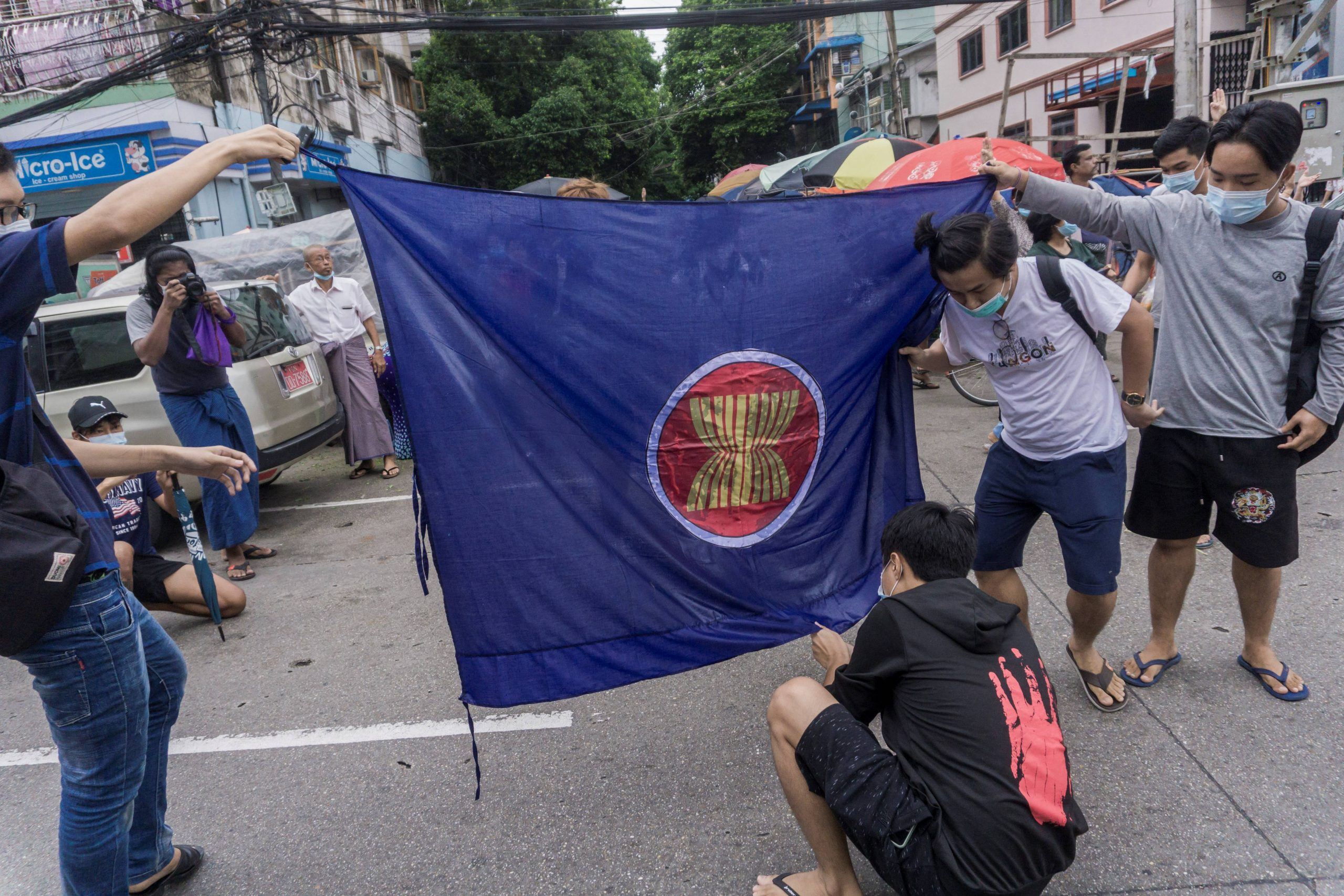 Protesters prepare to burn the flag of the Association of Southeast Asian Nations as they take part in a flash mob demonstration against the military coup in Yangon on June 14, 2021. (AFP)