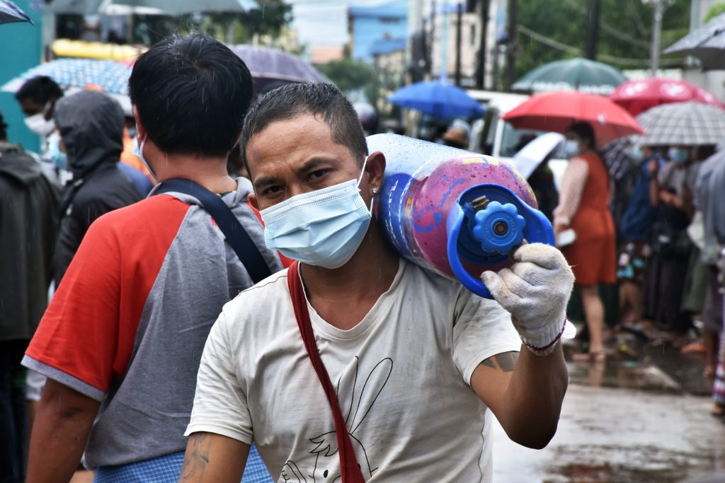 A man carries an oxygen cylinder outside the Matesat factory in South Dagon Township on July 13. (Frontier)