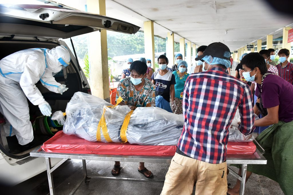 Volunteers and staff unload a body at the crematorium in Yay Way cemetery in Yangon's North Okkalapa Township on July 28. (Frontier)