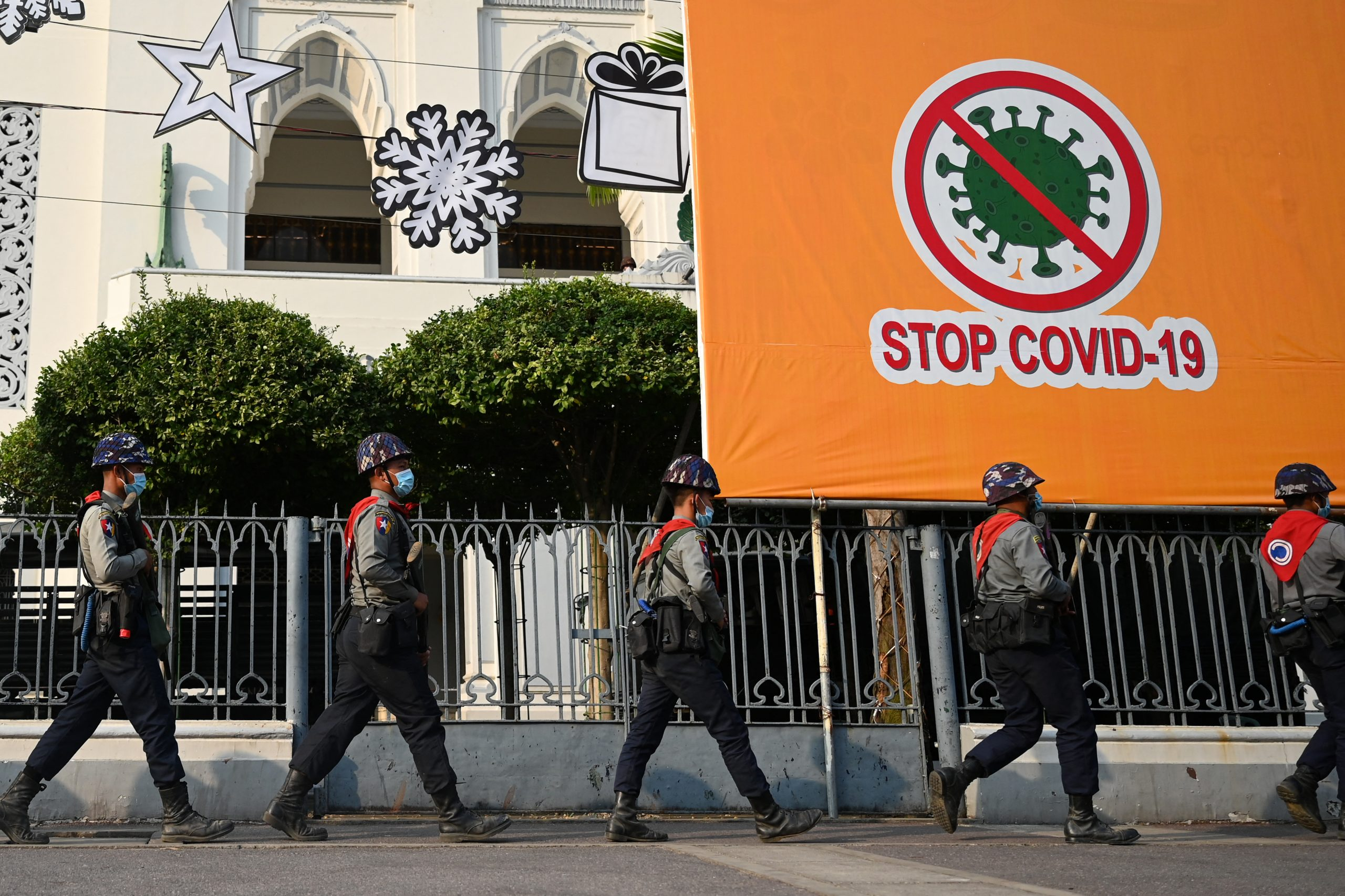 Police march past a billboard related to stopping the spread of COVID-19 as protesters gather for a demonstration against the military coup in Yangon on February 6. (AFP)