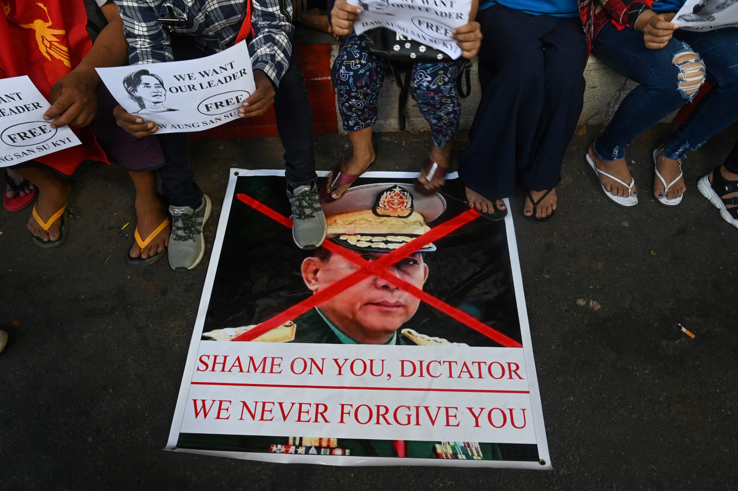Protesters step on a banner with an image of Senior General Min Aung Hlaing during a protest in Yangon on February 11. (Frontier)