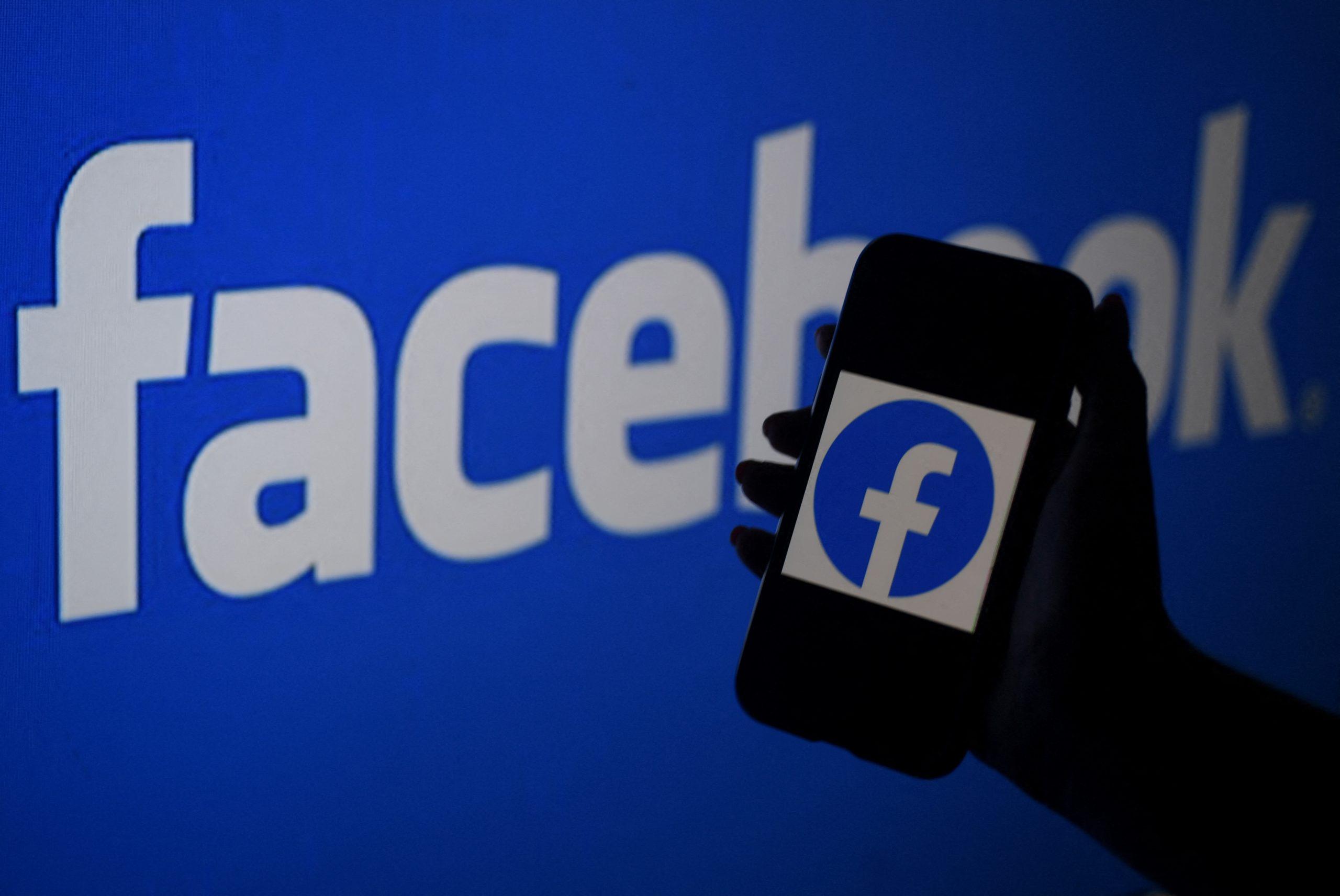 A smart phone screen displays the logo of Facebook on a Facebook website background in Arlington, Virginia on April 07, 2021. (AFP)