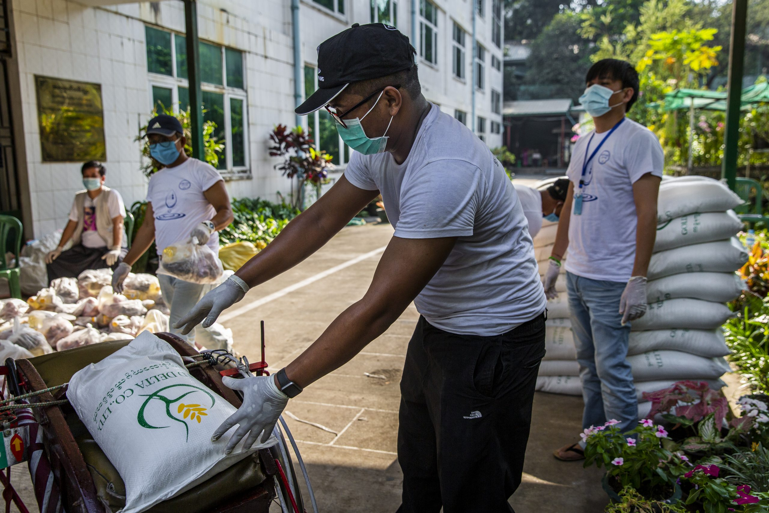 """A member of the """"Public to Public"""" charity group puts a bag of rice on a trishaw at a COVID-19 donation event in Yangon in April 2020. (Frontier)"""