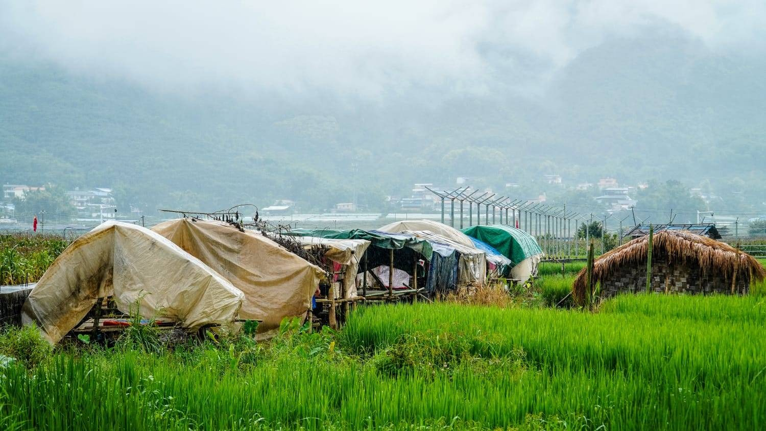 Families displaced by fighting in the Mong Ko area shelter in the town of Pang Hseng, with the newly built Chinese border wall in the background. (Mai Nyi Win Maung | Frontier)