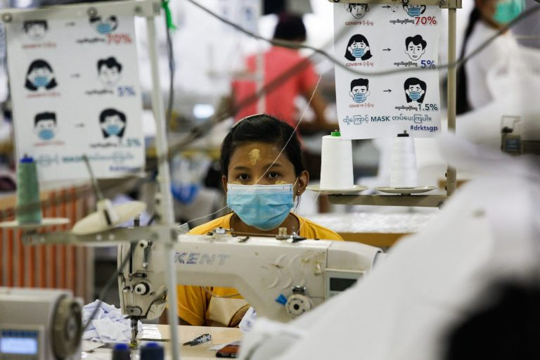 A worker sews disposable surgical gowns to protect health workers from COVID-19 at a garment factory in Yangon in May 2020. (AFP)