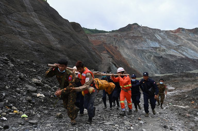 Myanmar soldiers and Red Cross workers carry a body recovered from the site of a landslide in Hpakant in Kachin State on July 4. (AFP)