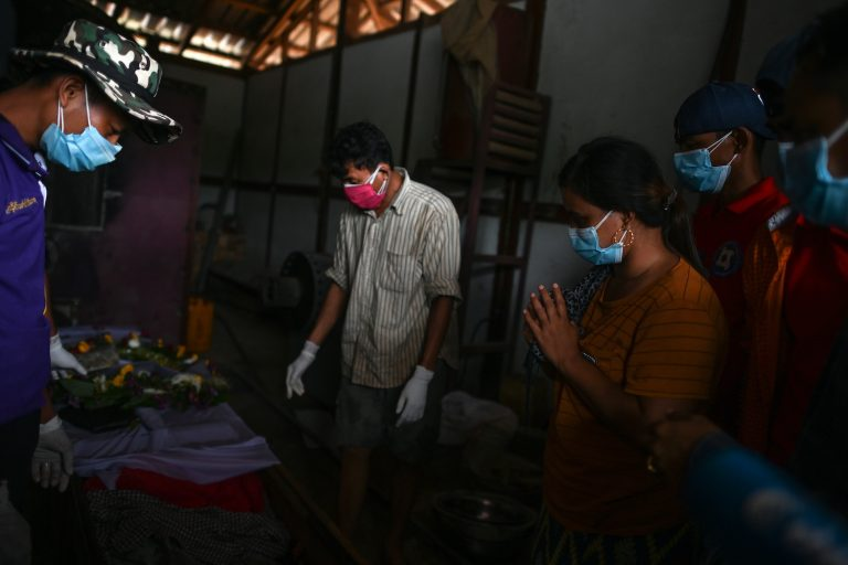 Ma Htar Htar Myint (second right) prays by the coffin of her husband Ko Than Naing before his funeral ceremony, following a deadly landslide in an area of open-cast jade mines, near Hpakant in Kachin State. (AFP)
