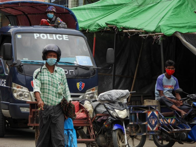 A policeman watches from a vehicle while people wear face masks in the Rakhine State capital Sittwe on August 23. (AFP)