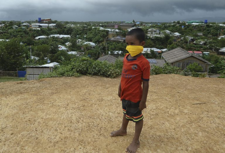 A young Rohingya refugee wearing a facemask as a preventive measure against COVID-19 stands on a hill in Kutupalong refugee camp on August 24. (AFP)